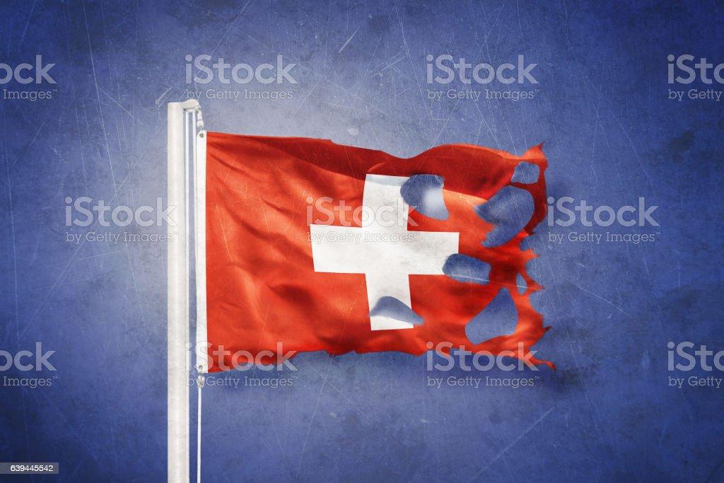 Torn flag of Switzerland flying against grunge background stock photo