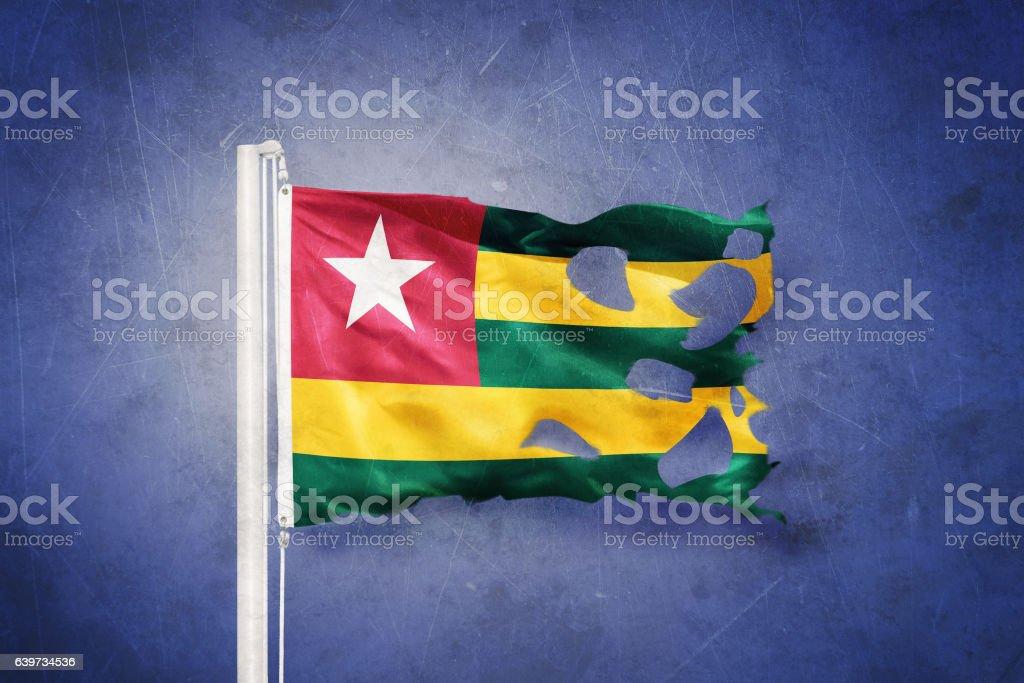 Torn flag of Togo flying against grunge background stock photo