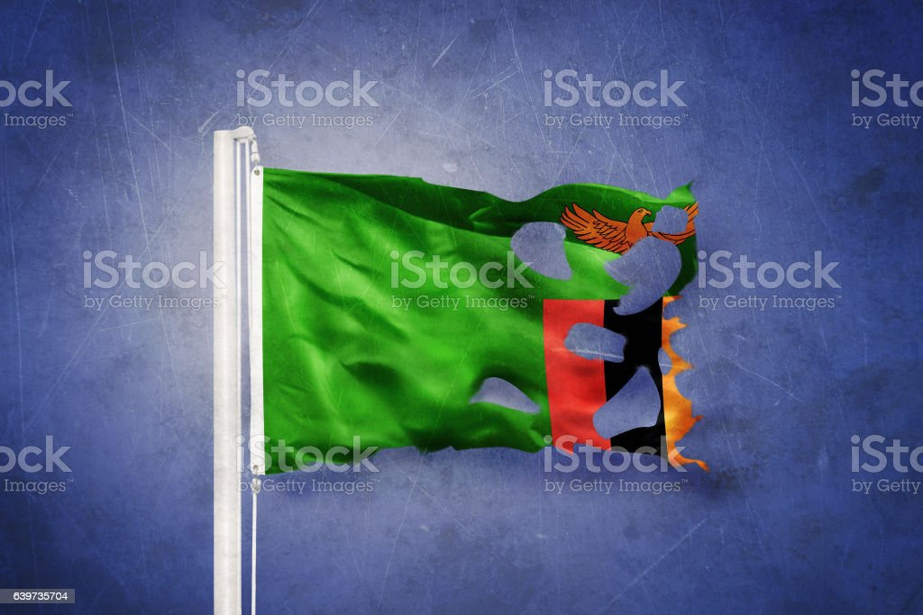 Torn flag of Zambia flying against grunge background stock photo
