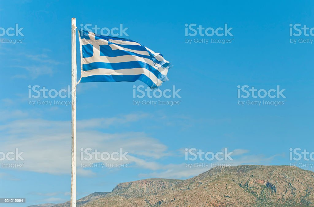 torn greek flag on flag-post against blue sky stock photo