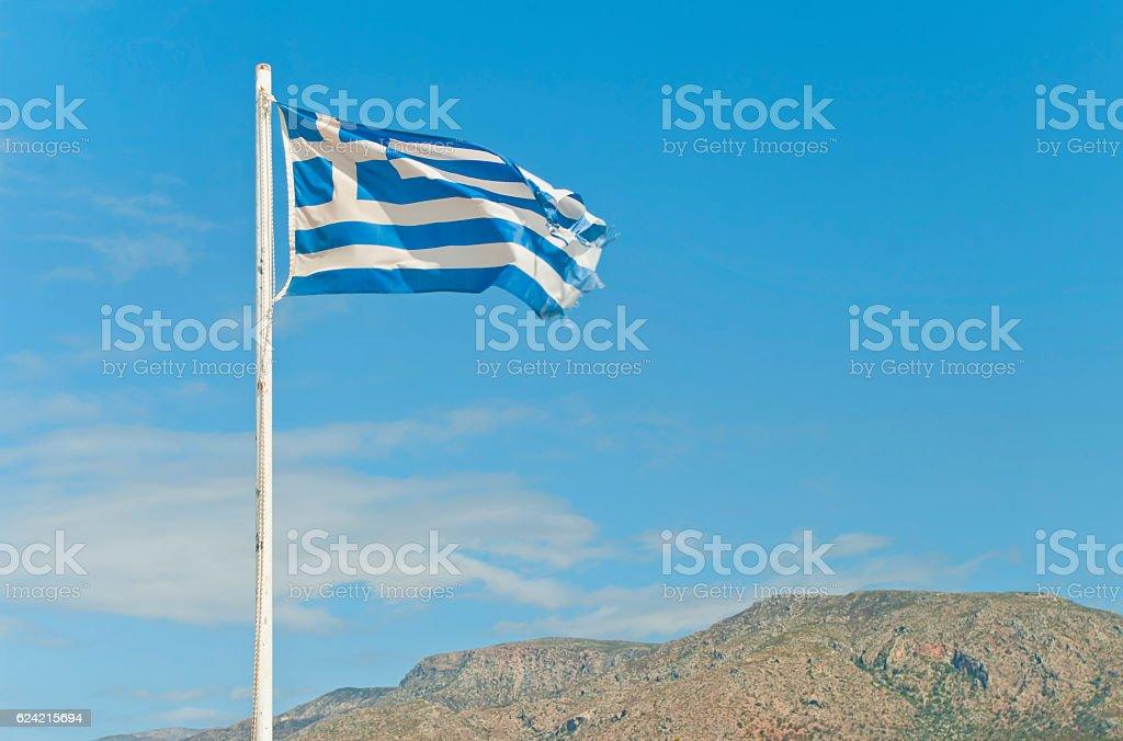 torn greek flag on flag-post against blue sky stock photo