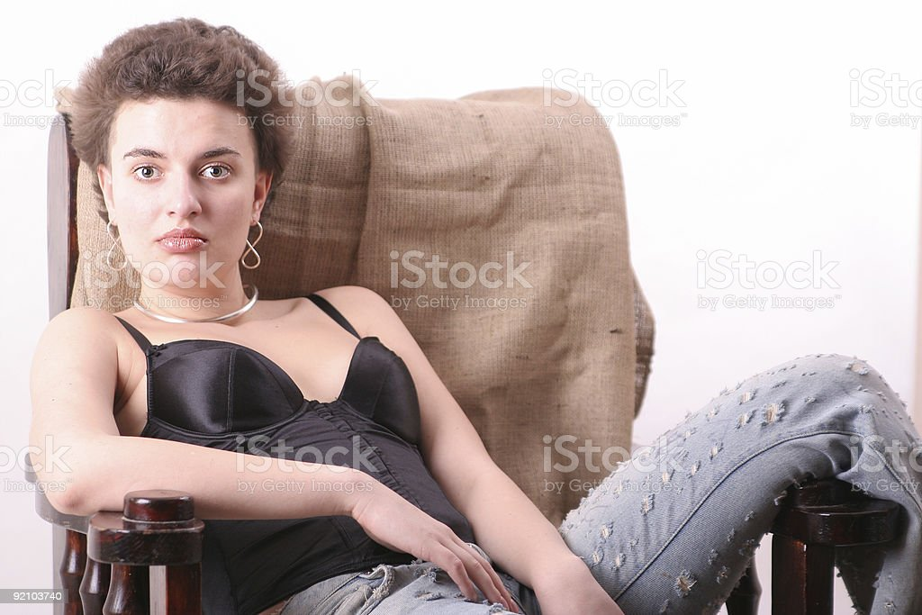 Torn jeans girl sit in arm-chair royalty-free stock photo