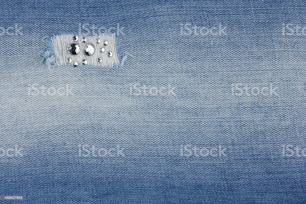 Torn light-blue jeans with rhinestones royalty-free stock photo