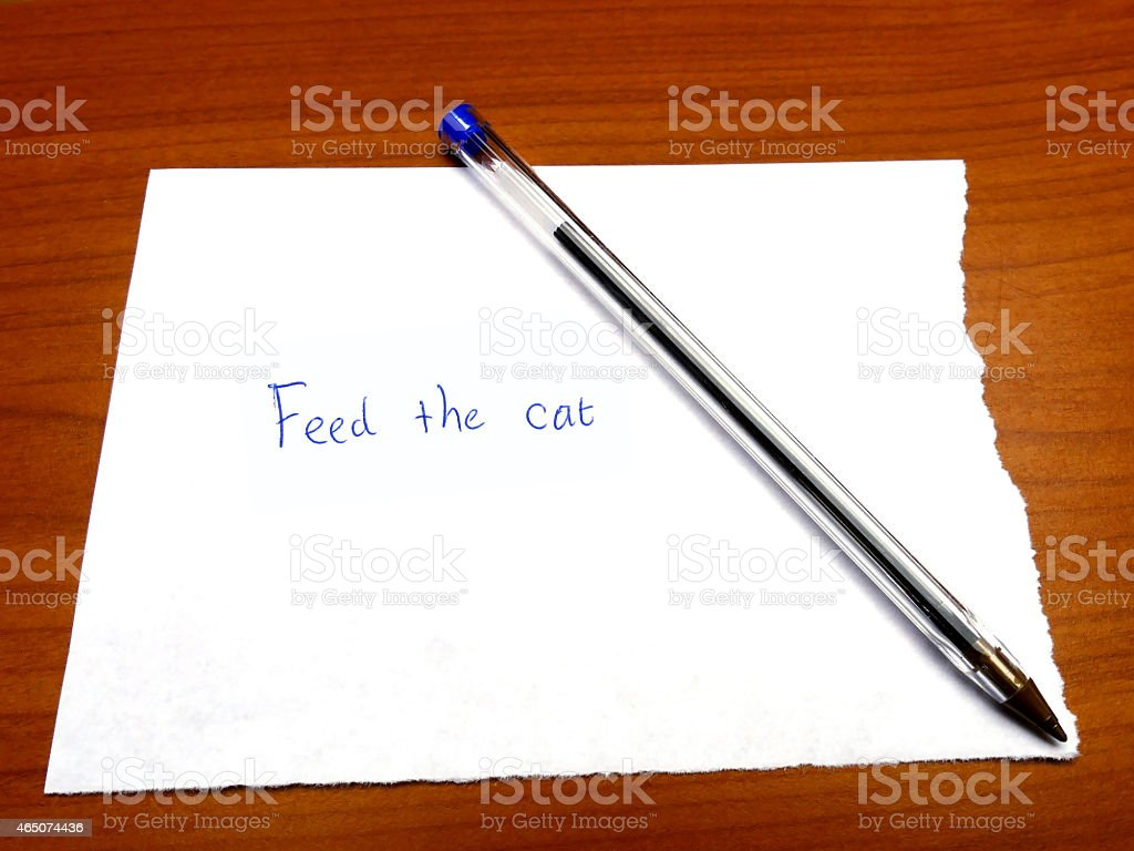 Torn paper note feed the cat on wood stock photo