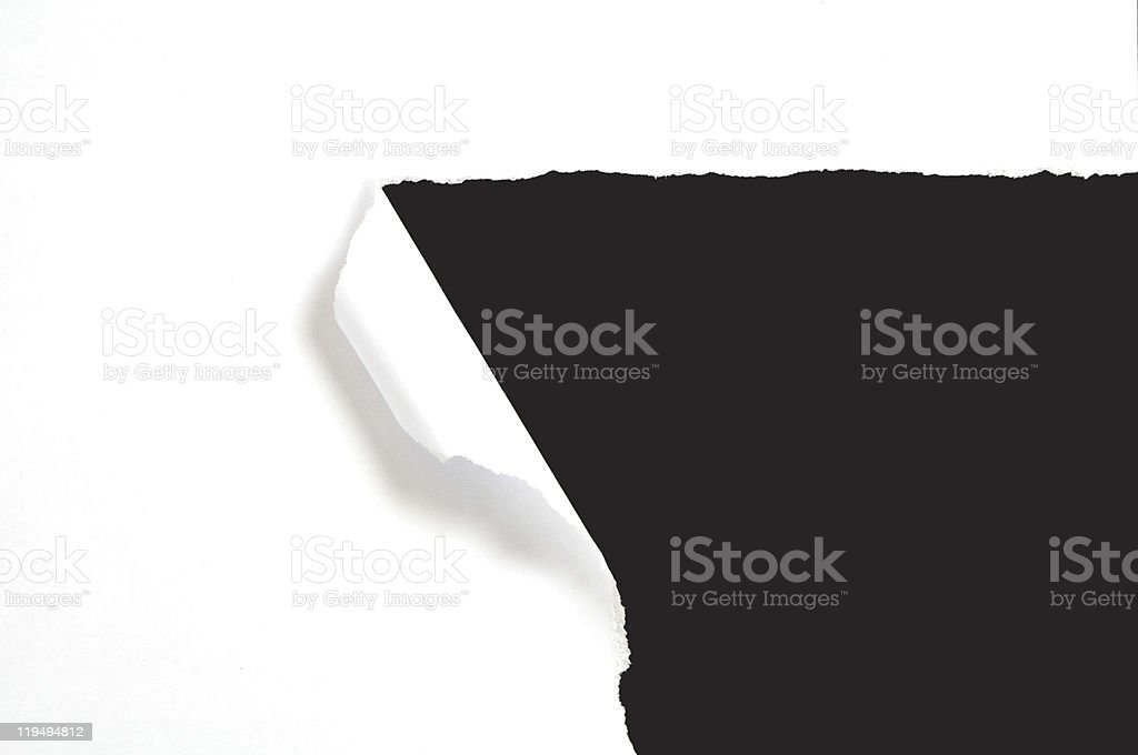 A torn white piece of paper revealing a black background stock photo