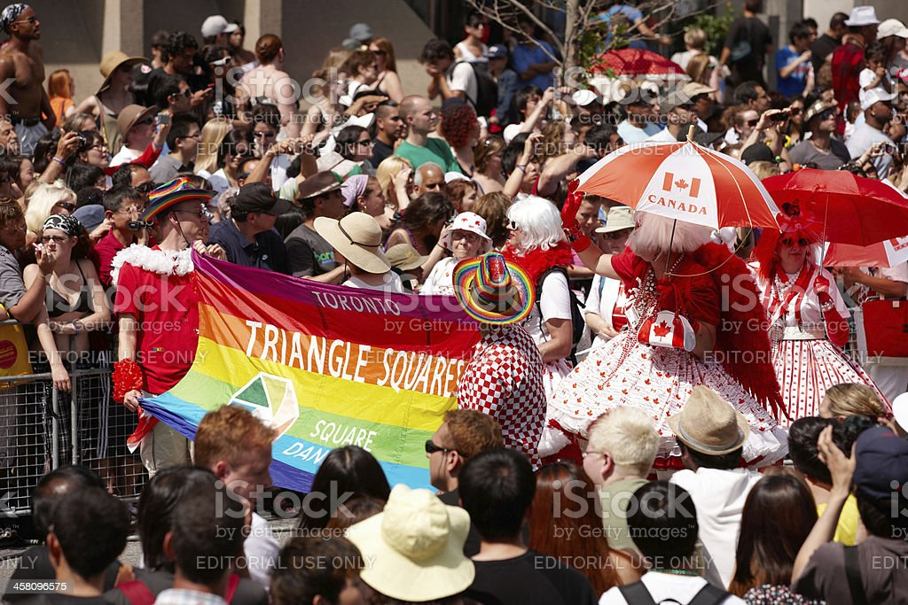 Toronto Gay Pride Parade participants with large multi-coloured flag royalty-free stock photo