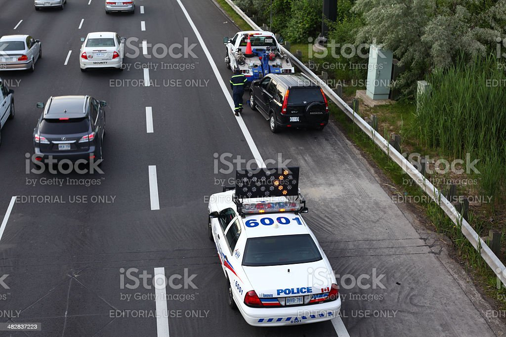 Toronto police car and CAA towing truck on a highway stock photo