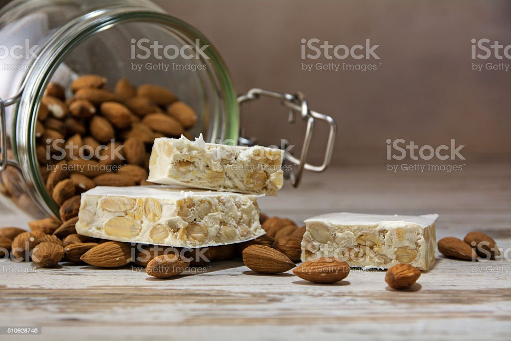 torrone or nougat and a glass jar with almonds stock photo