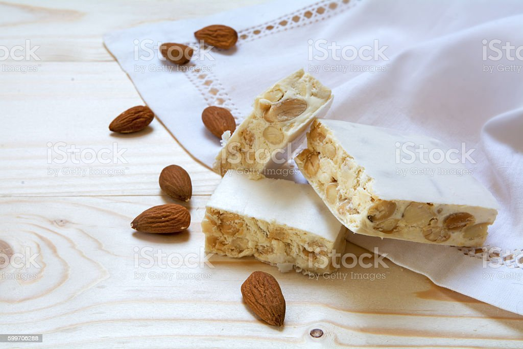 torrone or white nougat with almonds and napkin on wood stock photo