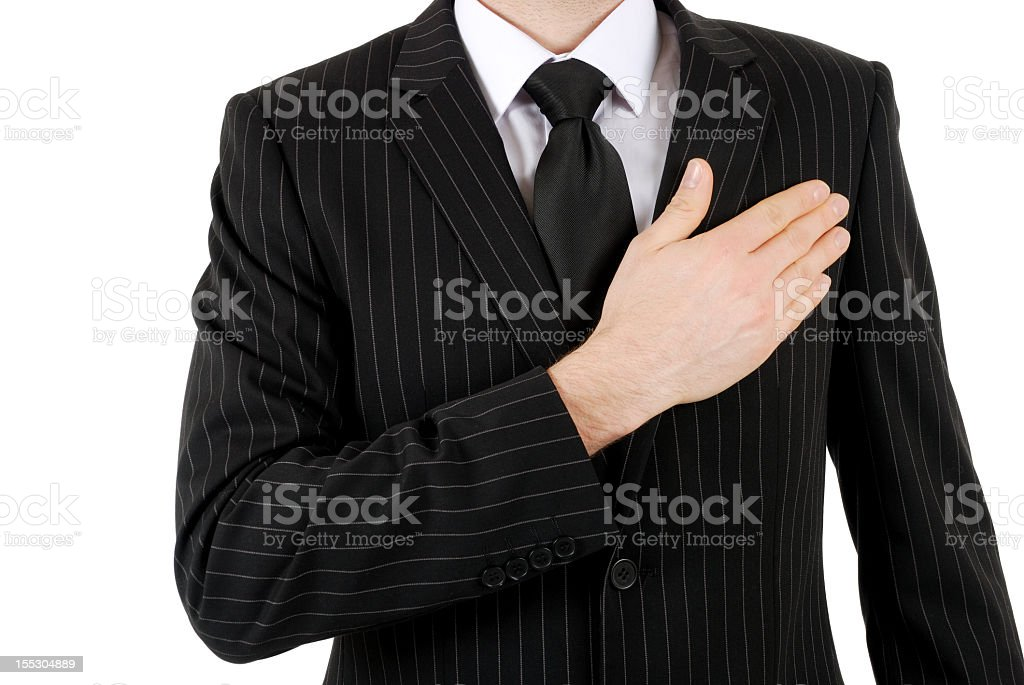 Torso of a man in pinstriped suit with his hand on his heart royalty-free stock photo