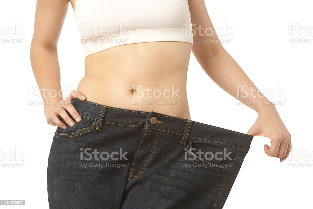 Torso of skinny woman in overweight jeans royalty-free stock photo