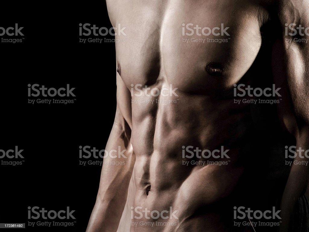 Torso of strong man against dark background royalty-free stock photo