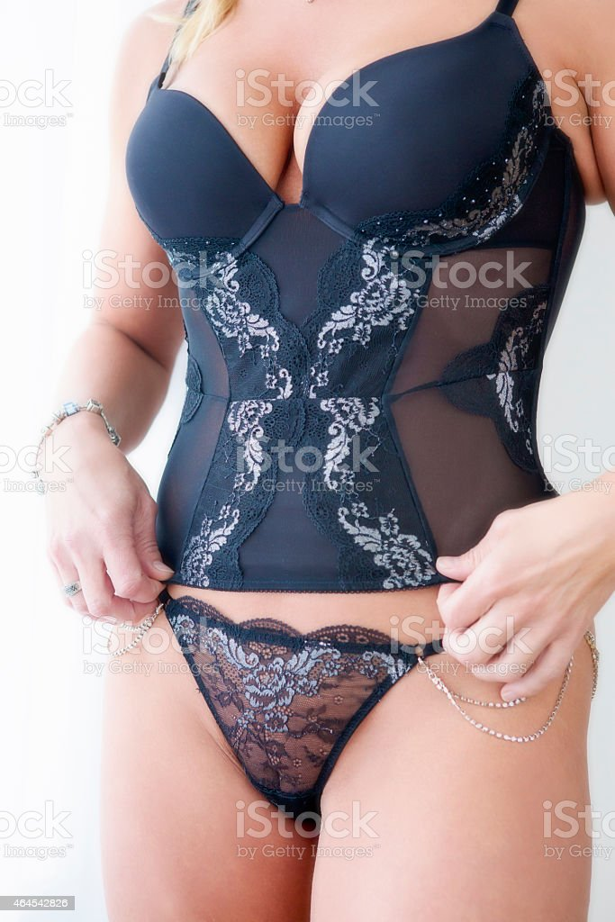 Torso of woman in black corset stock photo