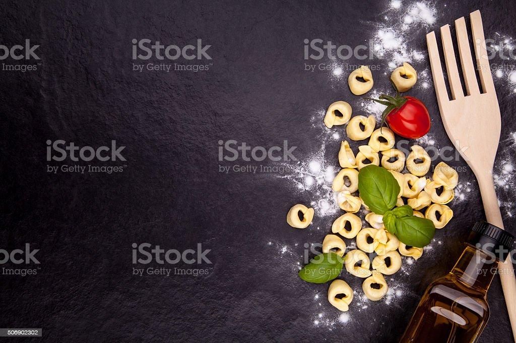 Tortellini de y harina en un negro placa de piedra. foto de stock libre de derechos