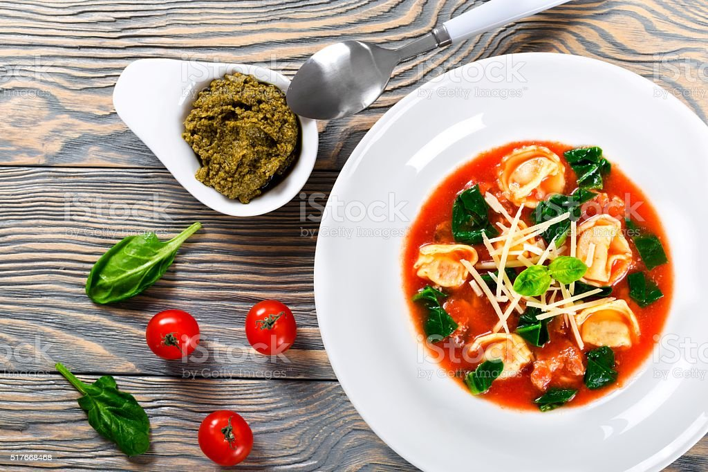 tortellini soup with italian sausages, spinach, tomato, parmesan cheese , pesto-sauce stock photo