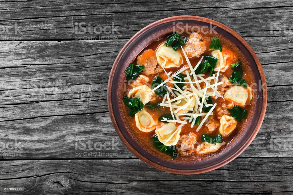 tortellini soup with italian sausages, spinach, tomato, parmesan cheese , top-view stock photo