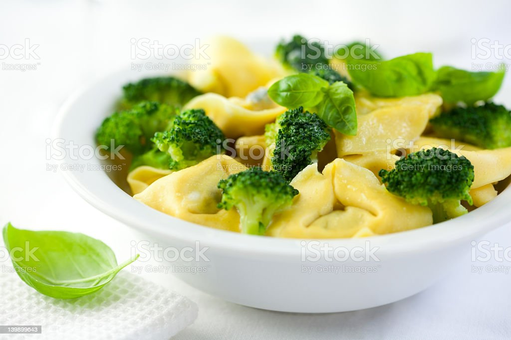 Tortellini with broccoli and fresh basil stock photo