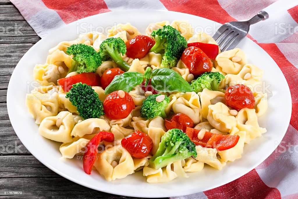 Tortellini with grilled cherry tomatoes, broccoli, red bell pepper, stock photo