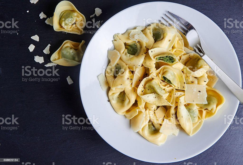 Tortellini with spinach and parmesan stock photo