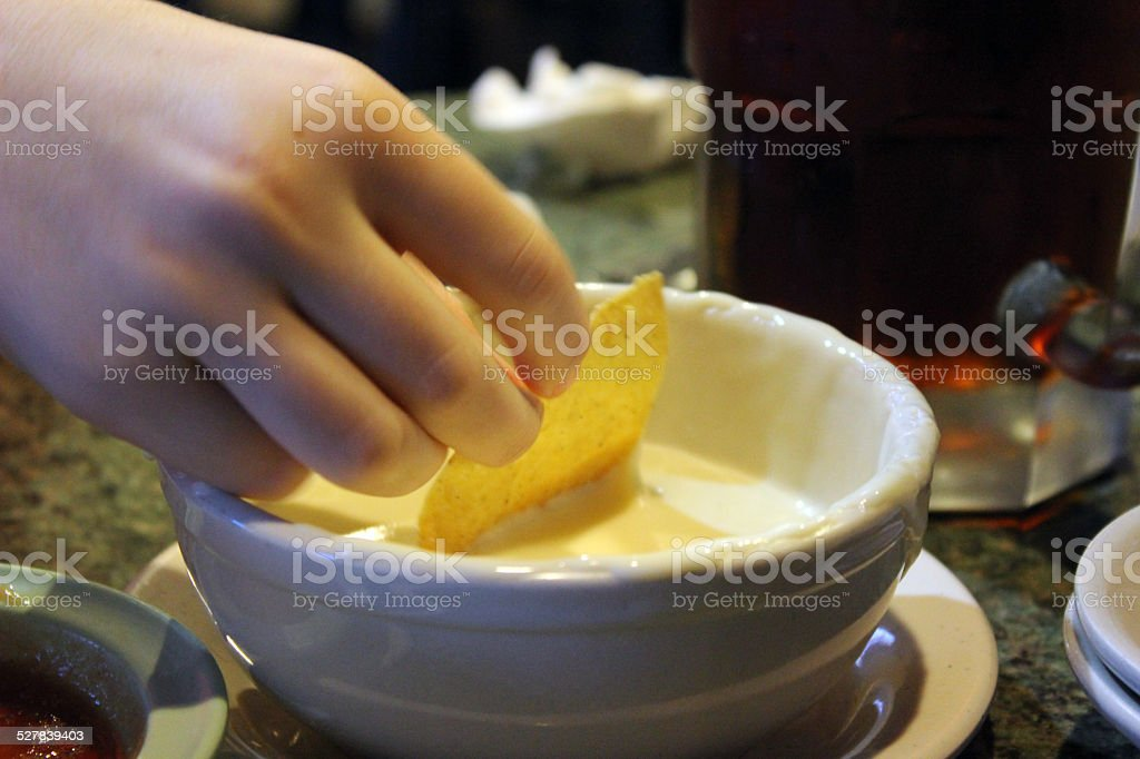 Tortilla Chip Dipping in Queso Cheese Sauce stock photo