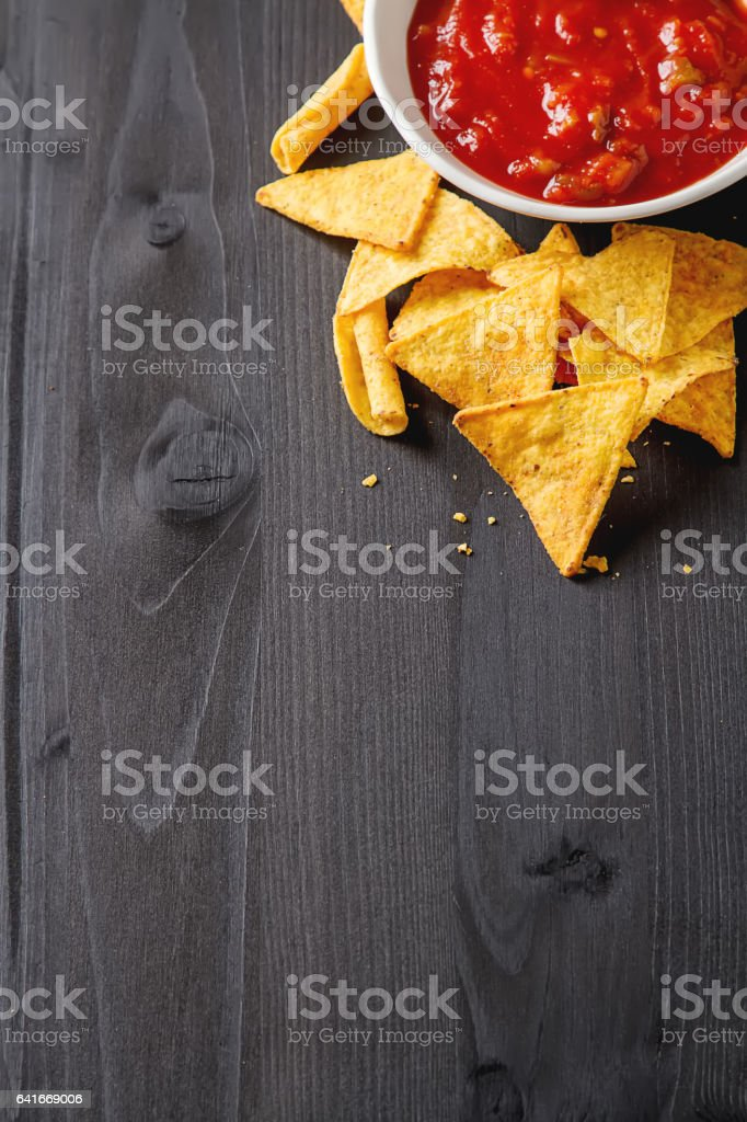 Tortilla chips on a blue plate with spicy tomato salsa. Mexican food. Dark wood background. stock photo