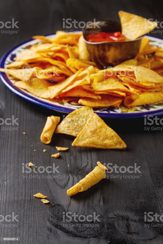 Tortilla chips on a blue plate with spicy tomato salsa. Mexican stock photo