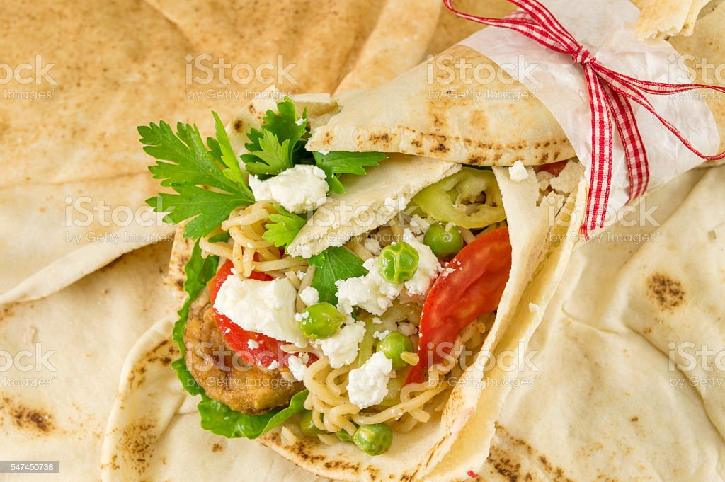 Tortilla filled with meat, noodles and vegetables. stock photo