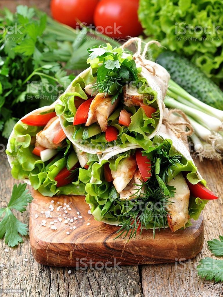 Tortilla roll with grilled chicken, tomato, cucumber, peppers, lettuce. stock photo