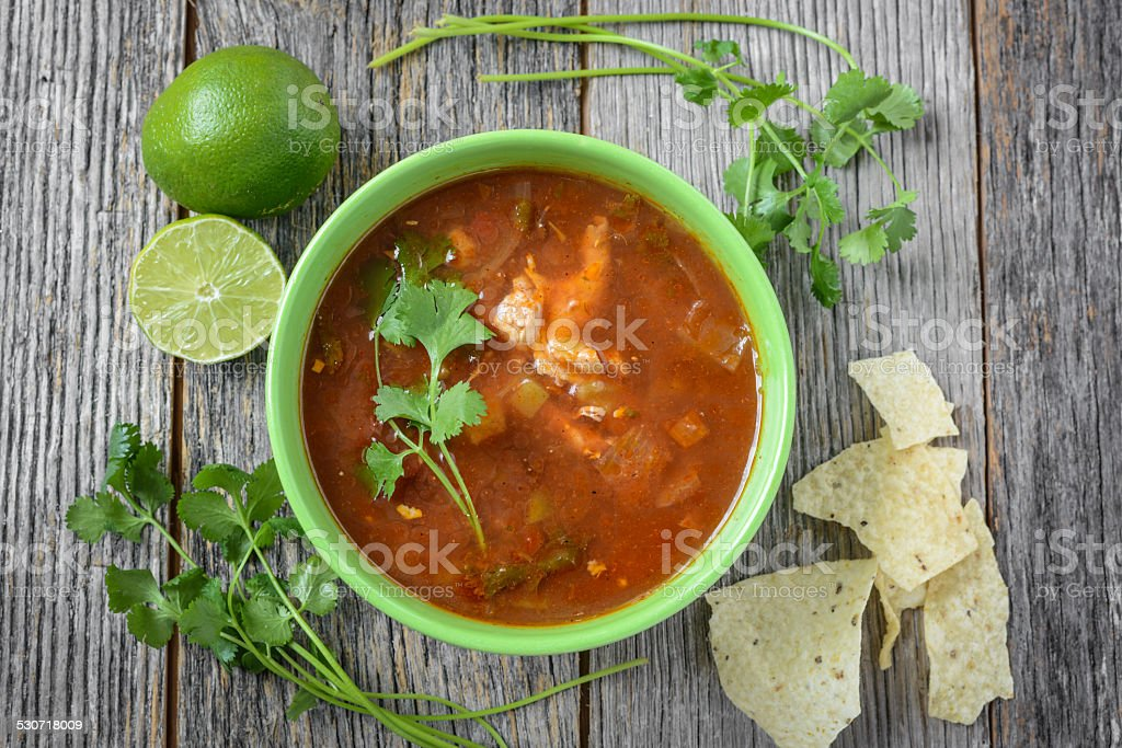 Tortilla Soup with Cheese, Lime, Cilantro and Wooden Spoon stock photo