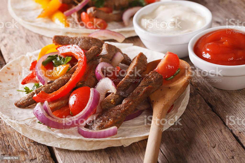 Tortilla with beef and vegetables close-up. Horizontal rustic stock photo