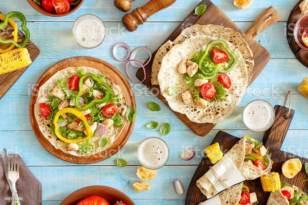 Tortilla with grilled chicken fillet, lager and grilled vegetabl stock photo