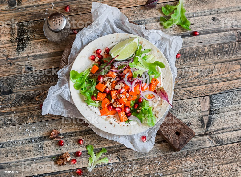 Tortilla with sweet potato, pomegranate and nuts. Delicious vegetarian snack. stock photo