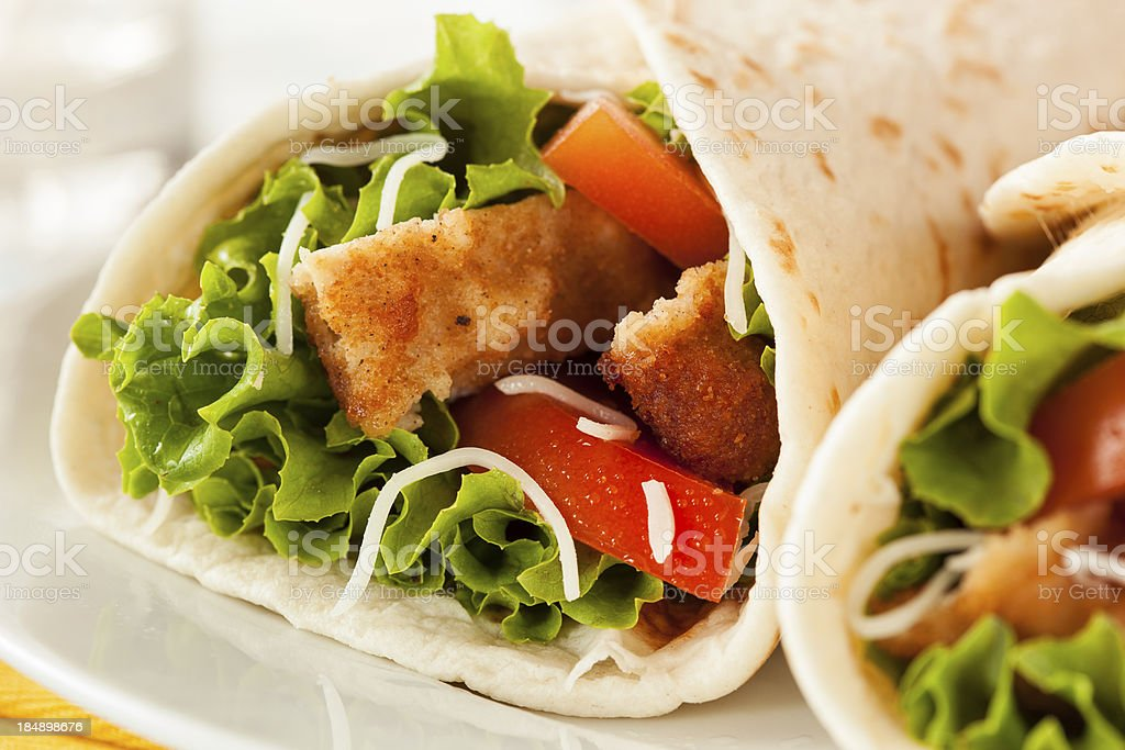 A tortilla wrap filled with breaded chicken and lettuce stock photo