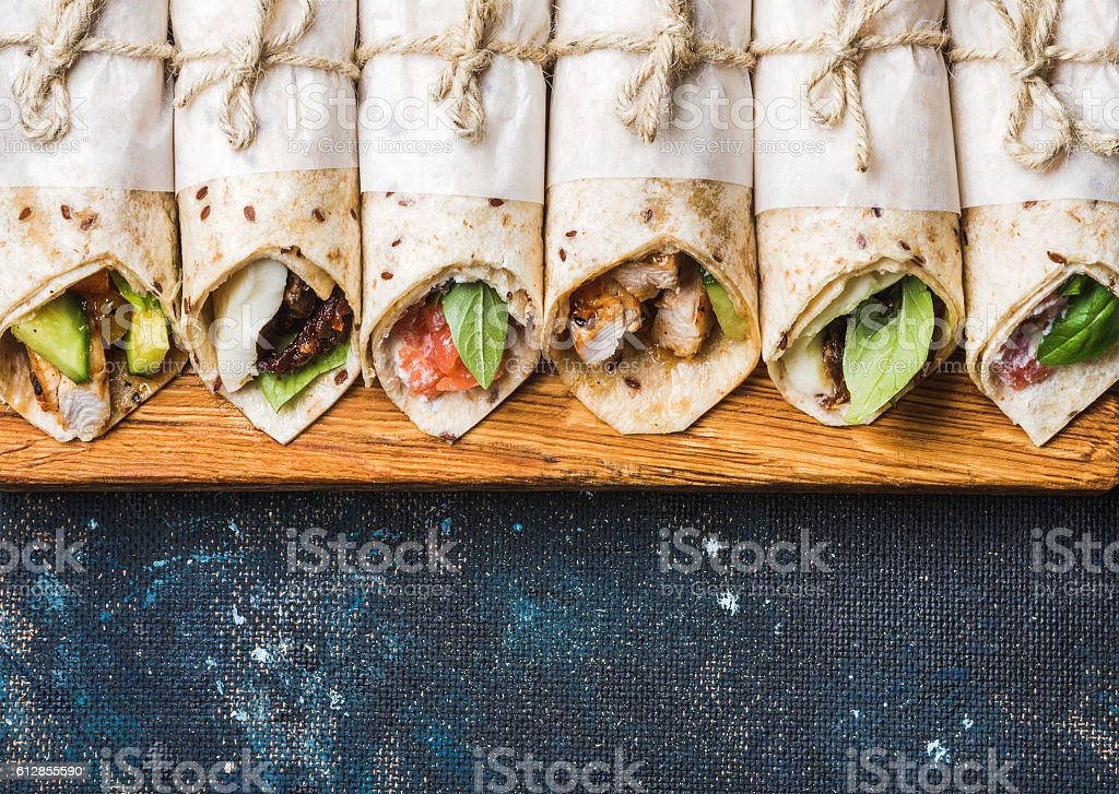 Tortilla wraps with different fillings on dark grey concrete background stock photo