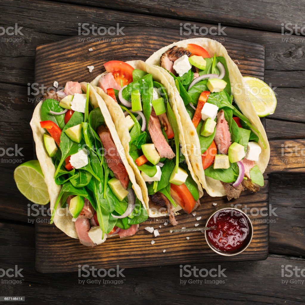 Tortilla wraps with grilled beef meat, spinach, avocado, tomato, pepper and feta cheese on wooden board on a dark wooden background stock photo