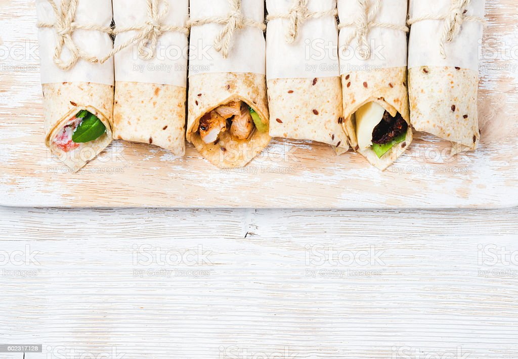 Tortilla wraps with various fillings on shabby white wooden board stock photo