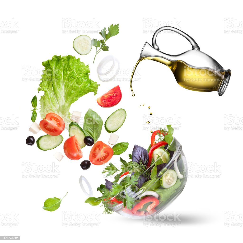 Tossed vegetables with oil being poured on them stock photo