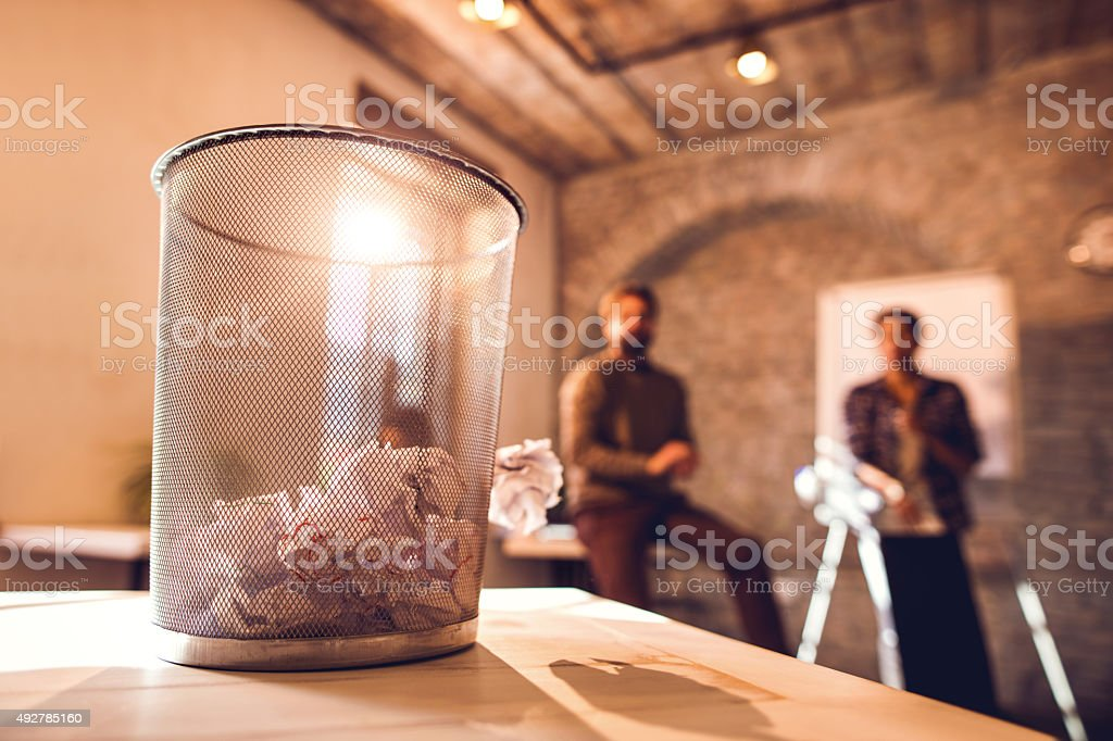 Tossing crumpled papers in wastepaper basket. stock photo