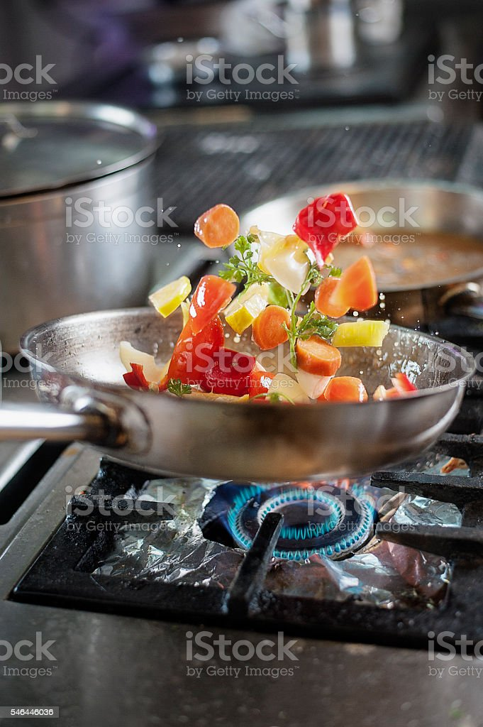 Tossing fresh vegetables in saucepan at kitchen stock photo