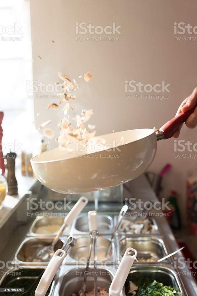 Tossing mushrooms in a wok pan stock photo