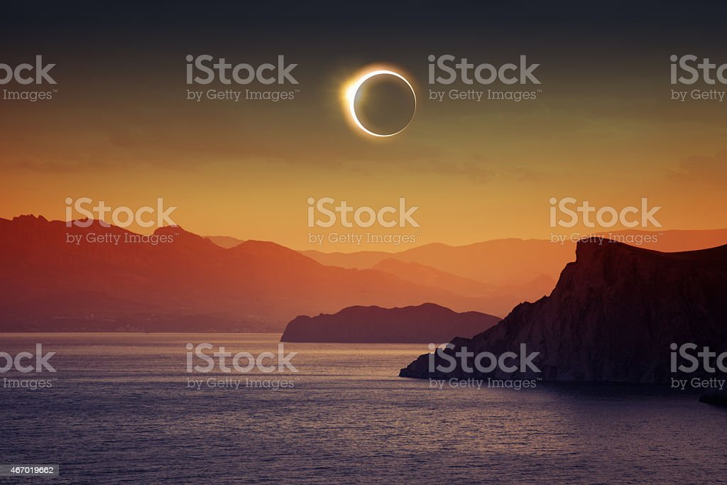 A total solar eclipse over water and mountains stock photo