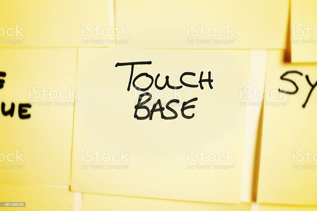 'Touch base' says adhesive note among others on noticeboard stock photo