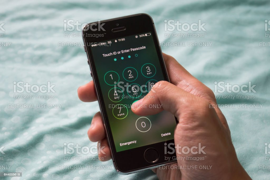 Apple iPhone5s held in one hand showing its screen with numpad for...