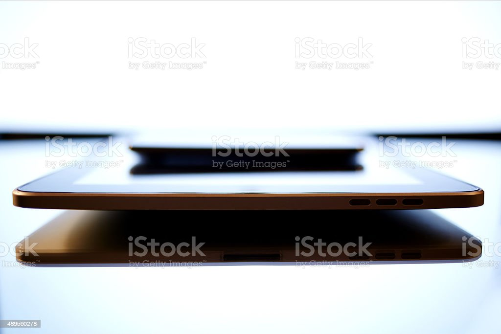 Touch pad and cell telepnohe lying on a office desk stock photo
