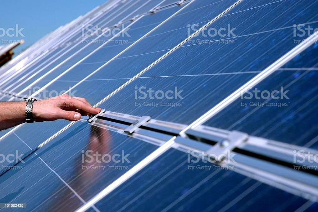 Touching a solar panel royalty-free stock photo