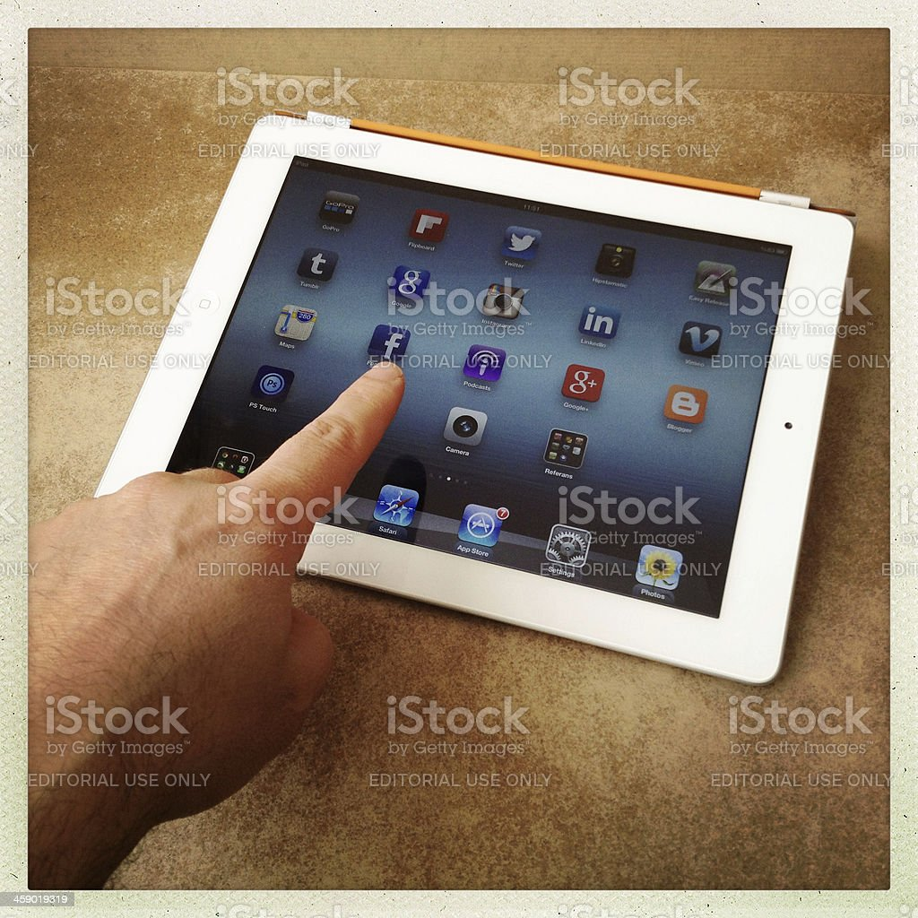 Touching the Facebook icon on iPad screen royalty-free stock photo