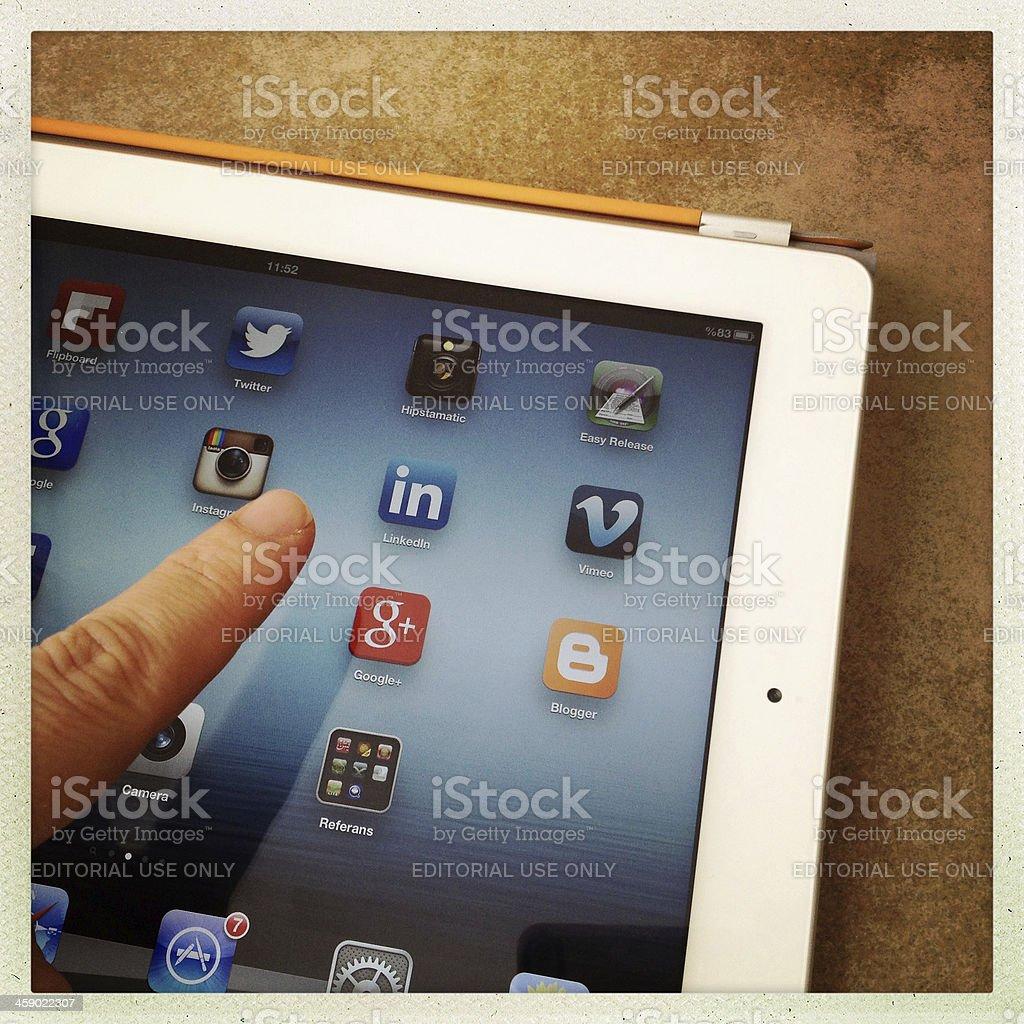 Touching the linkedn icon on iPad screen stock photo