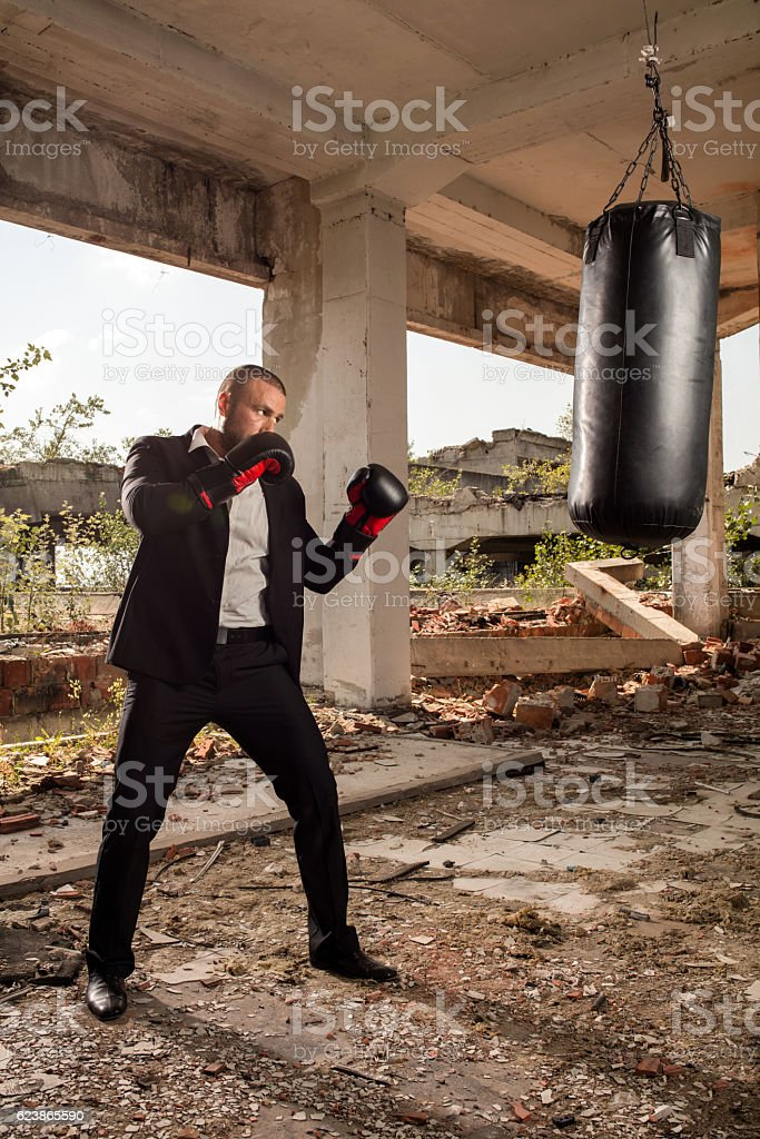 Tough businessman in a suit exercising among ruins. stock photo