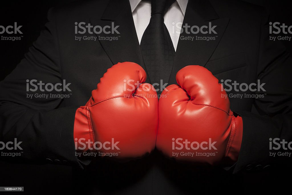 Tough businessman in black suit and red boxing gloves stock photo