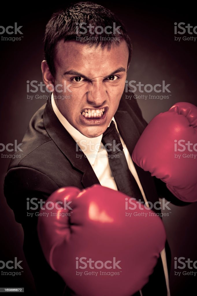 Tough businessman with boxing gloves royalty-free stock photo